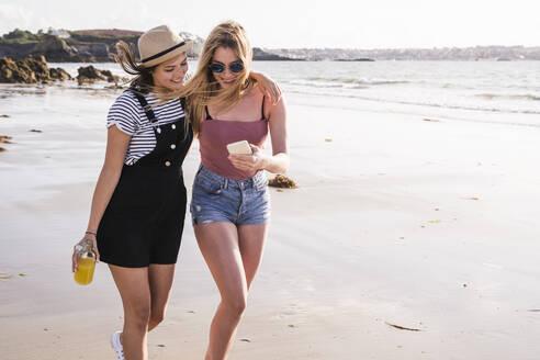 Two girlfriends having fun, walking on the beach, taking smartphone selfies - UUF19029