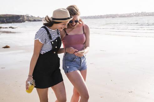 Two girlfriends having fun, walking on the beach, taking smartphone selfies - UUF19032