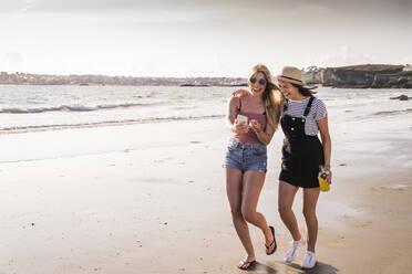 Two girlfriends having fun, walking on the beach, taking smartphone selfies - UUF19035