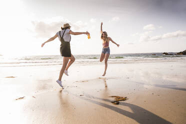 Two girlfriends having fun, running and jumping on the beach - UUF19038