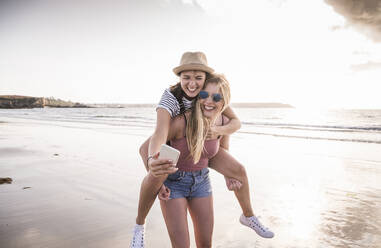 Two girlfriends having fun on the beach, carrying each other piggyback, taking smartphone selfies - UUF19044