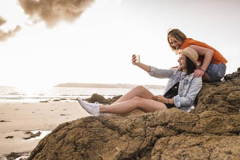 Two girlfriends sitting on rocky beach, taking smartphone selfies - UUF19047