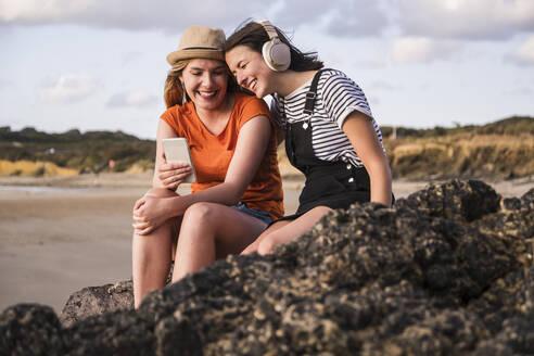 Two girlfriends sitting on rocky beach, using smartphone, listening miusic - UUF19053