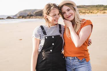 Two girlfriends having fun, walking on the beach - UUF19059