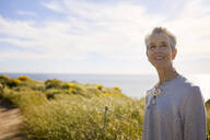 Thoughtful senior female tourist standing on cliff by sea against sky during summer - CAVF64929
