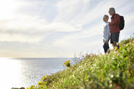 Side view of senior couple looking at sea while standing on cliff against sky - CAVF64947