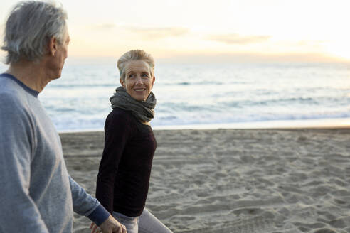 Side view of senior couple holding hands while walking at beach during sunset - CAVF64968