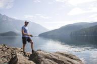 Man standing on rock fishing at Ross Lake in Washington State - CAVF65031