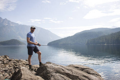 Man standing on rock fishing at Ross Lake in Washington State - CAVF65031