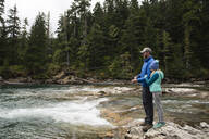 Father and Daughter Standing on Rocks Fishing on a River - CAVF65034