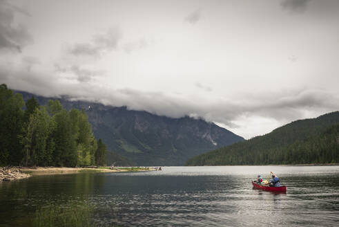 Man and Child Paddle a Red Canoe on a Mountain Lake on a Cloudy Day - CAVF65037