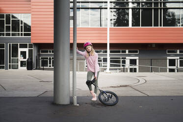 Young Girl Leaning on Column with Unicycle in Urban Environment - CAVF65043