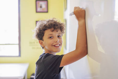Portrait of smiling boy drawing on a whiteboard - DLTSF00213