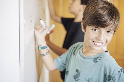 Portrait of smiling boy with a friend drawing on a whiteboard - DLTSF00216