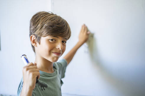 Portrait of confident boy in front of a whiteboard - DLTSF00219