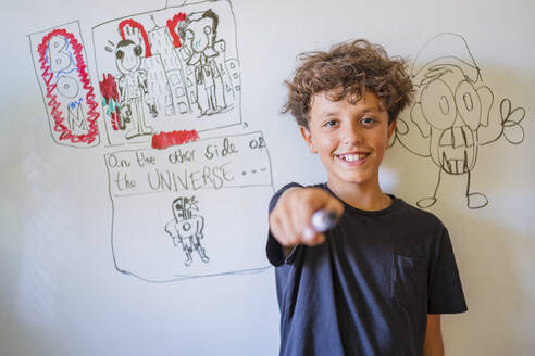 Portrait of happy boy in front of drawing on a whiteboard - DLTSF00231