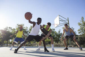 Young men playing basketball and dribbling ball on sports ground - ABZF02607