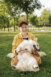Boy with Welsh Corgi Pembroke in a park - VPIF01590