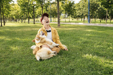 Laughing boy with Welsh Corgi Pembroke in a park - VPIF01593