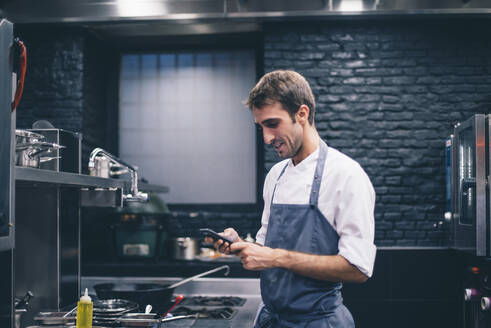 Chef using smartphone in the kitchen of a restaurant - CJMF00096