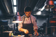 Chef serving food on plates in the kitchen of a restaurant - CJMF00105