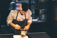 Chef serving food on a plate in the kitchen of a restaurant - CJMF00108
