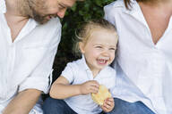 Happy little girl with a snack sitting amidst parents - MGIF00766