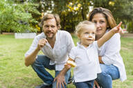 Parents with little daughter pointing her finger on a meadow - MGIF00769