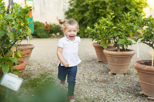 Happy little girl running along flower pots - MGIF00778