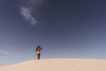 Nude young woman wearing a hat in the desert, Merzouga, Morocco - DAMF00131