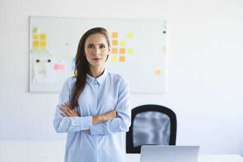 Portrait of confident businesswoman looking at camera with crossed arms in office - BSZF01470