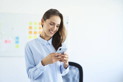 Smiling young businesswoman using smartphone in office - BSZF01473