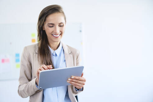 Young businesswoman using tablet in office and smiling - BSZF01482