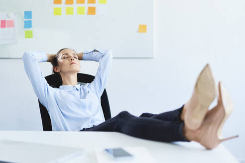 Young businesswoman relaxing in office reclining with feet on desk - BSZF01500