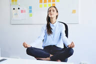 Young businesswoman sitting on office chair meditating - BSZF01503