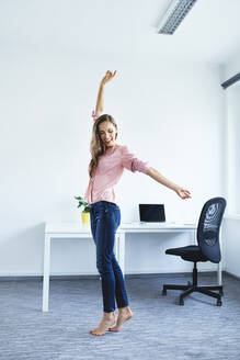 Cheerful young woman standing in office - BSZF01506