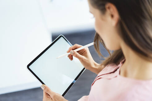 Over the shoulder view of woman drawing on tablet using pencil - BSZF01512