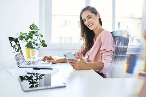 Young businesswoman checking phone while working in home office - BSZF01524