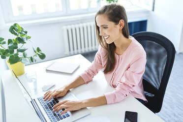 Smiling young woman working on laptop in home office - BSZF01527