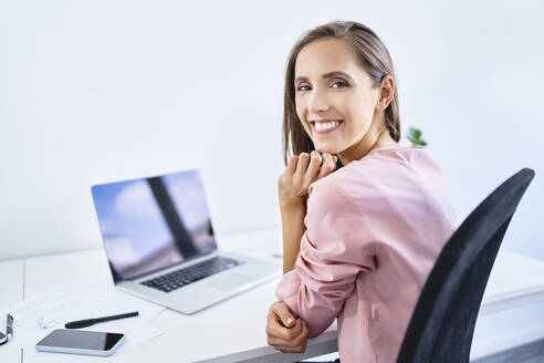 Cheerful young businesswoman smiling at camera while working in office - BSZF01530