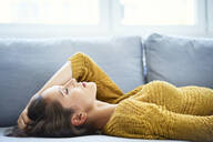 Young woman lying on sofa with eyes closed and relaxing - BSZF01542