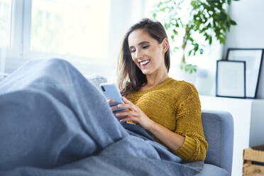 Cheerful young woman using phone and relaxing on sofa - BSZF01545