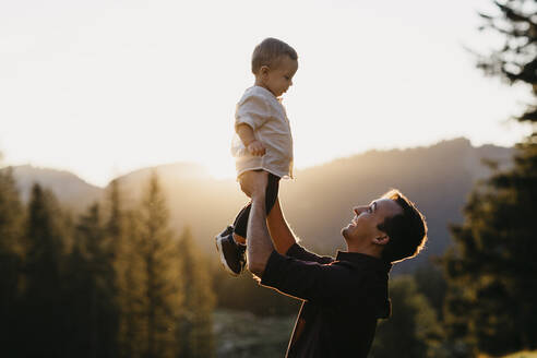 Happy father lifting up little son outdoors at sunset, Schwaegalp, Nesslau, Switzerland - LHPF01122