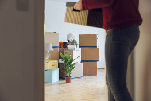 Woman carrying cardboard box in a new home - MAMF00794