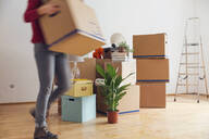 Woman carrying cardboard box in a new home - MAMF00797