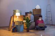Woman using laptop surrounded by cardboard boxes in a new home - MAMF00800