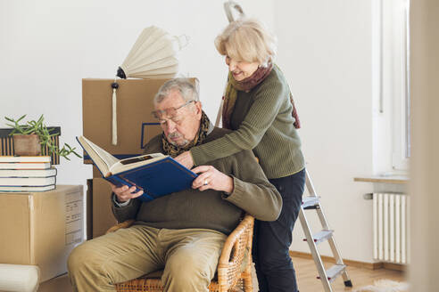 Senior couple looking at photo album surrounded by cardboard boxes in an empty room - MAMF00812