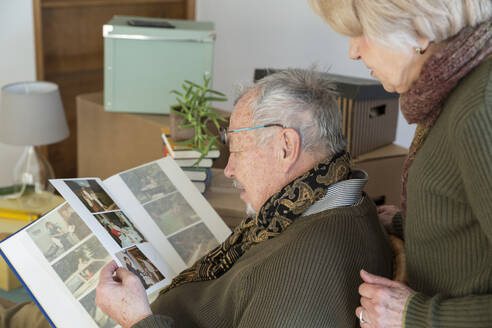 Senior couple looking at photo album surrounded by cardboard boxes in an empty room - MAMF00815