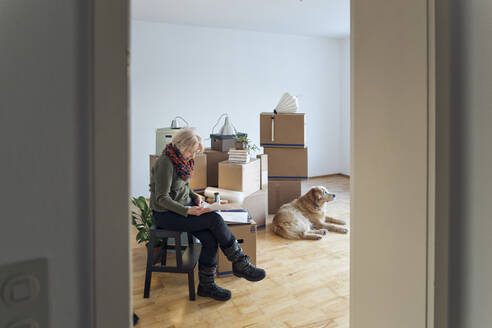 Senior woman looking at papers surrounded by cardboard boxes in an empty room - MAMF00827
