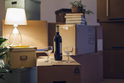 Wine bottle and glasses on cardboard box in an empty room in a new home - MAMF00830